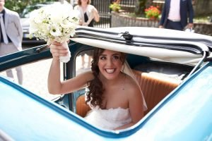 Sposa in auto con bouquet in mano